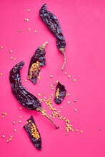 Dried Pasilla Chile Peppers On Pink Background.