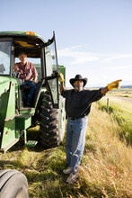 Senior Male Farmers Talking And Pointing At Tractor In Sunny Field