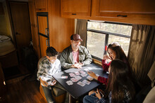 Family Playing Cards On Table In RV