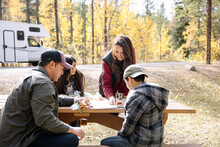 Family Looking At Map On Picnic Table In Forest