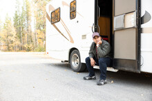Man Sitting In Doorway Of RV
