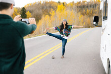 Man Taking Photo Of Woman Doing Yoga In The Middle Of The Road In Fore