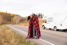 Couple Kissing Under Blanket In Front Of RV