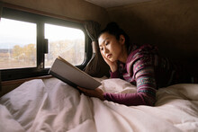 Woman Reading Book In Bed In RV