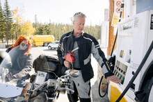 Motorcyclists Refuelling At Gas Station