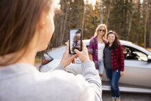 Woman Taking Photo Of Friends Next To Car In Forest