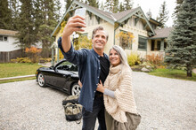 Man Taking Selfie With Wife Next To Car And Vacation Rental