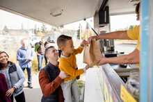 Man Carrying Son, Taking Bag From Food Truck Owner