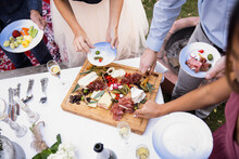 Overhead View Of Guests Having Cheese And Cured Meat Platter At Party