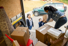 Family Unloading Cardboard Boxes From Moving Van