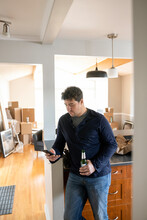 Man Taking Break From Moving With Smart Phone And Beer