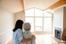Affectionate Daughter Hugging Senior Mother In Empty New Home