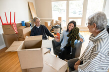 Senior Parents Watching Daughter Unpack Old Stuffed Animal In New Home