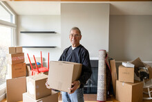 Portrait Confident Senior Man Moving Boxes In New Home