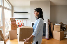 Woman With Cardboard Box Moving Into New Home