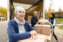 Happy Senior Woman Unloading Cardboard Boxes From Moving Van