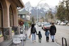 Family Walking Along Sidewalk In Front Of Mountains