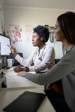 Female Doctor Explaining Test Results To Patient In Consultation