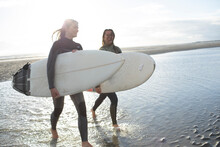 Young Female Surfers Wading In Sunny Ocean Surf With Surfboards