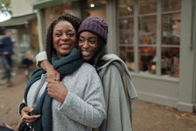 Portrait Happy Mother And Daughter Hugging On Sidewalk