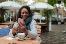 Happy Woman With Coffee Using Smart Phone At Table On Cafe Patio