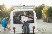 Portrait Young Female Surfer Putting On Sweater At Sunny Camper Van