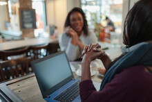 Businesswomen Meeting At Laptop In Cafe