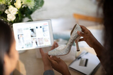 Women With Wedding Shoe Shopping For Ideas On Digital Tablet