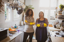 Portrait Confident Mother And Daughter Cleaning Kitchen