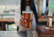 Close Up Female Bartender Serving Pint Of Beer In Pub