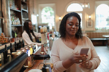 Woman Using Smart Phone At Bar