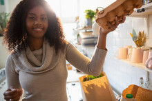 Portrait Smiling Woman Unpacking Groceries In Kitchen