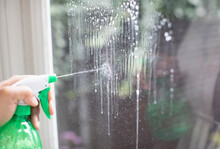 Close Up Cleaning Window With Spray Bottle Glass Cleaner