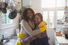 Portrait Happy Mother And Daughter In Rubber Gloves Hugging In Kitchen
