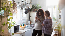 Mother And Daughter Using Smart Phones In Kitchen