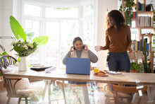 Daughter Serving Coffee To Mother Working At Laptop On Dining Table