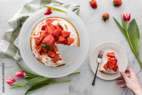Fotografie, Obraz Top down view of a strawberry shortcake with a hand holding a plate with a slice of cake on it