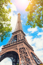 Eiffel Tower Against The Sky With Green Trees In Paris, France. Famous Travel Destination.