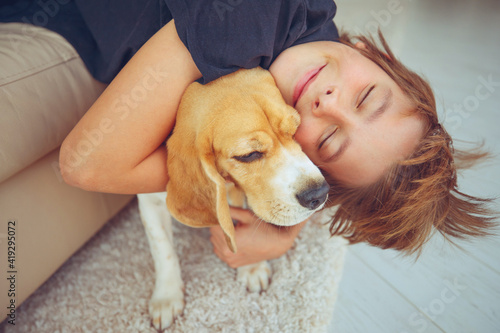 Fotografia Happy boy and dog Beagle hugs her with tenderness, smiles, looks at the camera at home