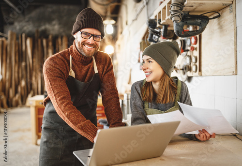 Cheerful joinery owners discussing project on laptop