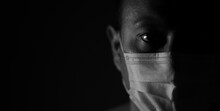 Covid-19 Pandemic Awareness. In The Dark Low Key Monochrome Male Profile Wearing Protection Face Mask.