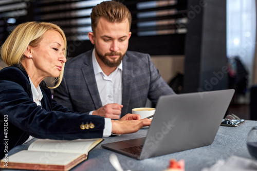 Fototapeta business partners have conversation and talking at meeting in restaurant, they sit with laptop at table, co-working, wearing formal clothes obraz na płótnie