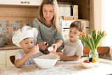 mother and sons little boys baking cookies in kitchen, doing dough for easter cake