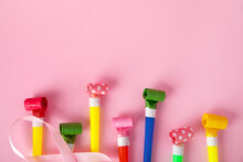 Birthday Party Whistles On Pink Background, Colorful Celebration With Party Blower Horns, Minimal Party Concept.