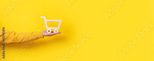 Fotografía Trolley on hand over yellow background, panoramic image