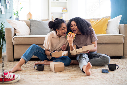 Foto Portrait of young sisters indoors at home, eating burgers.