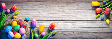 Easter - Decorated Eggs In Nest With Colorful Tulips On Wooden Plank