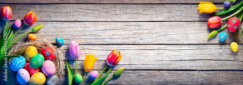 Obraz Easter - Decorated Eggs In Nest With Colorful Tulips On Wooden Plank - fototapety do salonu