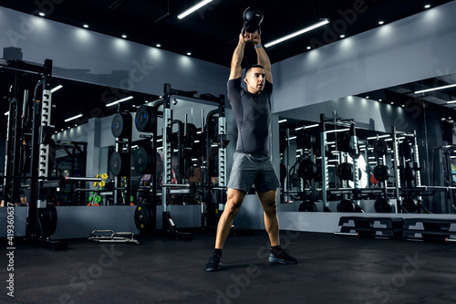 Obraz A powerful man lifts a kettle bell above his head in the fitness center with strong movements.The concept of functional cross-fit training. Energy boost - fototapety do salonu