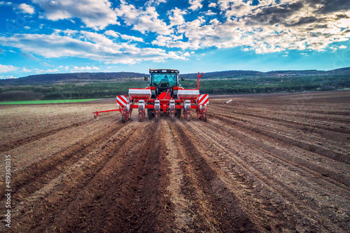 Foto Farmer with tractor seeding crops at field